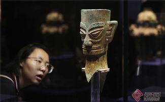 一名观众在《国宝盛宴--<史记>中的西南边疆》展上观看来自四川广汉三星堆博物馆的商代铜人头像。