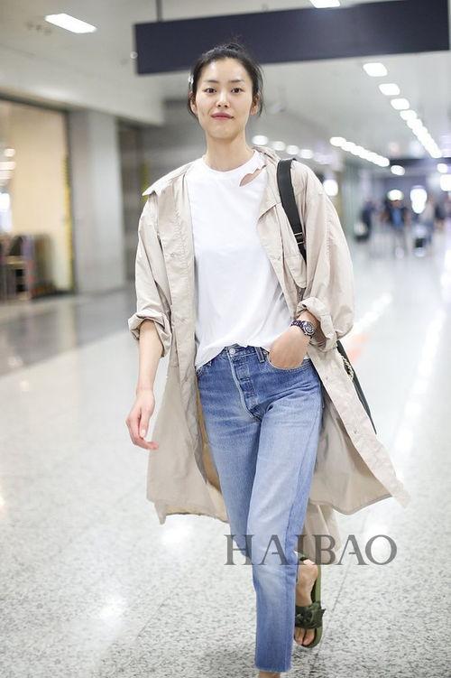 新浪娱乐讯6月22日,大表姐刘雯身着牛仔裤、白t、长风衣现身机场,扎丸子头少女感爆棚,见镜头露迷人笑容.